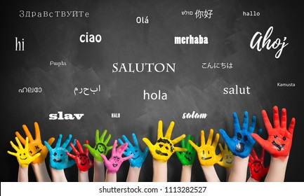 "painted kids hands in front of a blackboard with the word ""hello"" in many languages"