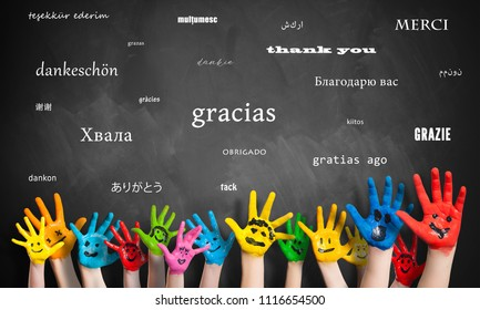 "painted kids hands in front of a blackboard with the message ""thank you"" in many languages"