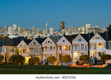 Painted Ladies with San Francisco skyline in the background as seen from Alamo Square with city lights