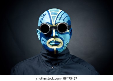 The painted man's face on a black background. Dark goggles