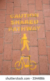 Painted markings indicating a pathway that is shared by pedestrians and bicycles