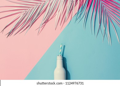 Painted palm leaves and cold drink on pastel pink and blue background with copy space. Tropical summer concept. Minimal flat lay.