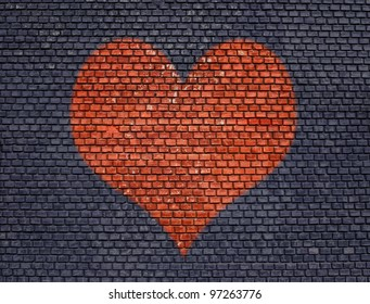 Painted red big heart on old brick wall