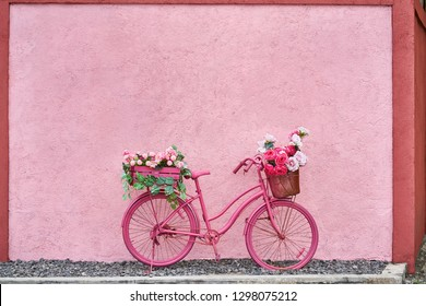 Painted saturated pink bicycle with baskets with flowers and green leaves stands on the pebble on the background of the textured colorful wall outdoors. Horizontal.