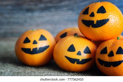 Painted scary faces on a holiday of halloween on orange fruits
