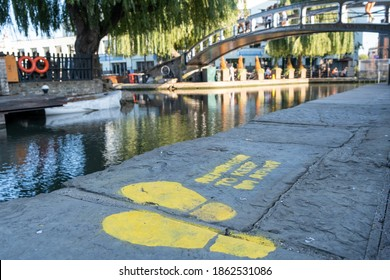 A painted sign on the floor asking people to social distance next to Regents Canal with a bridge in the background at Camden Market
