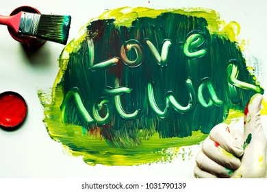 Painted sign reading love not war, with thumbs up. Image is highly colorful with a mixture of hues.