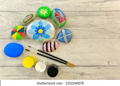 Painted  stones with paintbrush and paint pots on a shabby board background