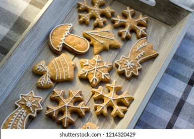 Painted traditional Christmas gingerbreads arranged on wooden tray in daylight, common tasty sweets for holidays, various shapes, snowflakes, comets and bell, white sugar icing painting