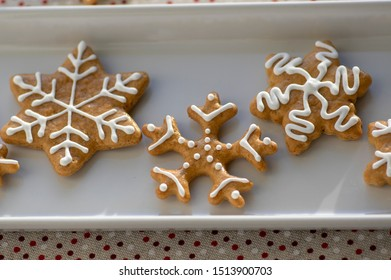 Painted traditional Christmas gingerbreads snowflakes and stars arranged on white dish in daylight, dotted tablecloth, common czech tasty sweets