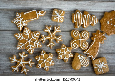 Painted traditional Christmas gingerbreads snowflakes and stars arranged on wood table in daylight, common czech tasty sweets