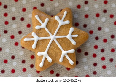 Painted traditional Christmas star gingerbread arranged on dotted tablecloth, common czech tasty sweets, one piece