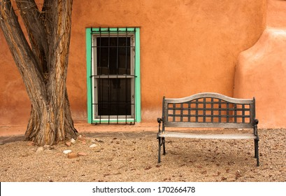Painted turquoise window, tree and bench in Taos, New Mexico