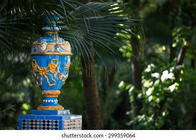 A painted vase in the lush vegetation of a public park in Seville, Spain