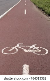 Painted white bicycle on special paved part of road in sunlight.