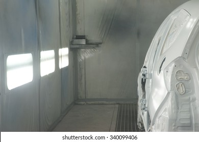A painted white car in a booth spray.
