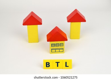 Painted wooden arrows and house with a BTL 'Buy To Let' sign in front to symbolize financial rewards of investment.
