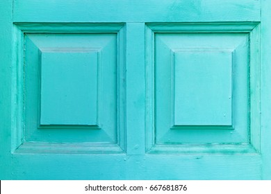 Painted wooden door in azure color with geometric elements in close-up