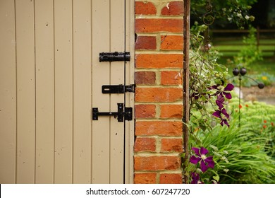 Painted wooden garden door leading to shed with brick wall and sweet pea flowers