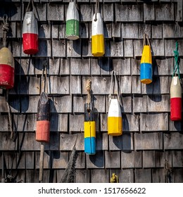 Painted wooden lobster pot marker buoys hanging on a cedar shake shingle wall