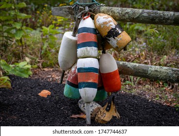 Painted wooden lobster pot marker buoys hanging on weathered fence post