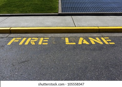 A painted yellow color on the curb and the word fire lane on the ground is for the fire department to park their fire trucks