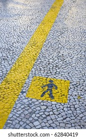 Painted yellow walk line, in the stone floor of an urban city, Lisbon, Portugal