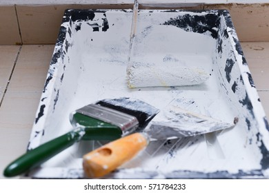 Painter accessories with paintbrush,box and scraper on the floor.
