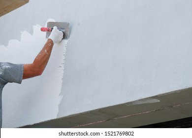 Painter applying fresh paint on the house facade