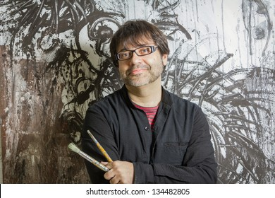 Painter artist with black glasses posing in front of his mural paint