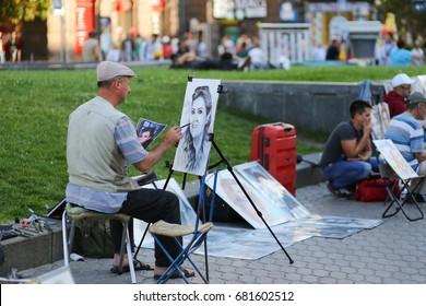 Painter (artist) drawing a portrait (caricature) of a woman - Ukraine, Kiev - July 17, 2017