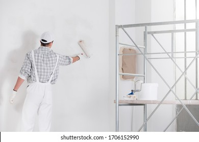 Maler oder Erbauer, der eine Wand mit weißer Farbe und eine Walze von hinten mit einer Leiter neben einem DIY-, Renovierungs- oder Konstruktionskonzept malte