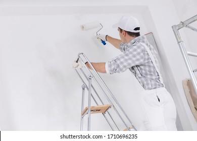 Maler oder Erbauer, der eine weiße Wand auf einer Leiter gemalt, mit einer Walze in Nahaufnahme, während er arbeitet