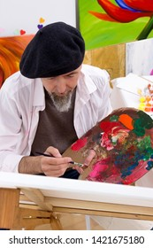 Painter concentrates at work on an easel