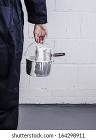 Painter / decorator holding paint bucket with brush in front of painted wall portrait