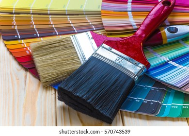 Painter and decorator work table with house project, color swatches, painting roller and paint brushes