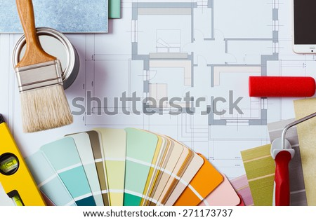 Painter and decorator work table with house project, color swatches, painting roller, brush and tools, top view