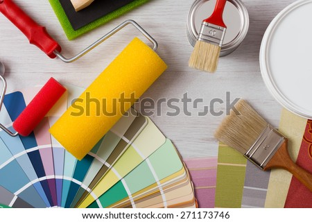 Painter and decorator work table with house project, color swatches, painting roller and paint brushes, top view