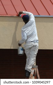 Painter, dressed in white, stands at the top of his ladder to reach the last big of trim that needs painting.