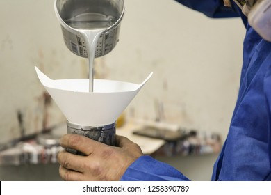 painter fills the paint in the spray gun through a funnel with a filter. the paint is poured into a paper funnel with a filter. a jet of gray automotive paint spills from the can