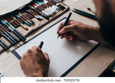 Painter, graphic designer or calligraphy artist sits at table with different kinds of tools, brushes, marker and pen, open his pencil or brush with black ink ready to create new design on white canvas