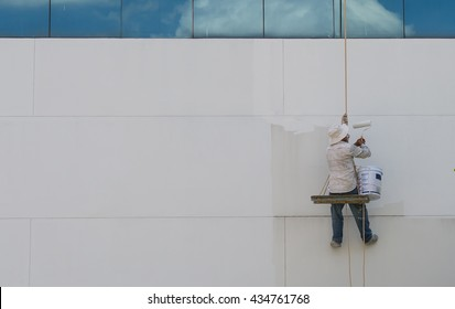 Painter hanging from harness painting a wall