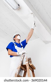 painter with helmet, gloves and mask painting ceiling with paint brush on wooden vintage ladder, bottom view