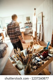 A painter in his studio working on a canvas, focus on the brushes in the foreground