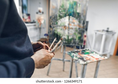 Painter holds a brush and a palette knife in the background of the easel with the host and a palette of oil paints. Artist's hands with brushes close-up on a background of artistic studio.Oil painting