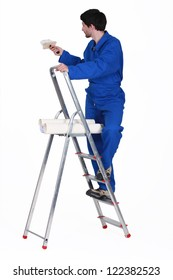 painter in jumpsuit on ladder isolated on white