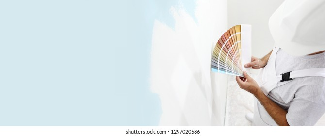 painter man with color swatches in your hand, choice of colors concept, on big blank wall for copy space and web banner background