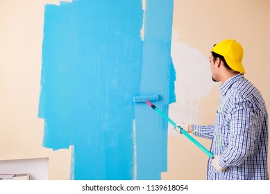 Painter man painting the wall at home