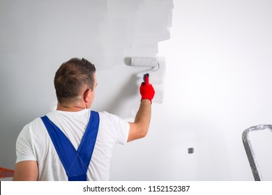 Painter man at work with a paint roller