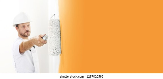 painter man at work with a paint roller, wall painting concept, view from top on big copy space template